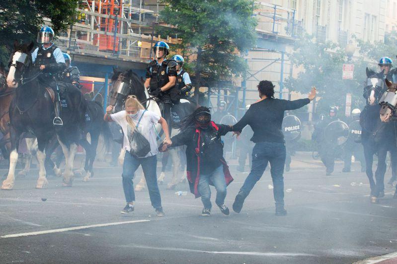 美國警方1日用催淚瓦斯驅逐白宮外的和平示威者,讓總統川普能順利走到白宮對面的聖約翰座堂拿聖經供媒體拍照。(法新社)