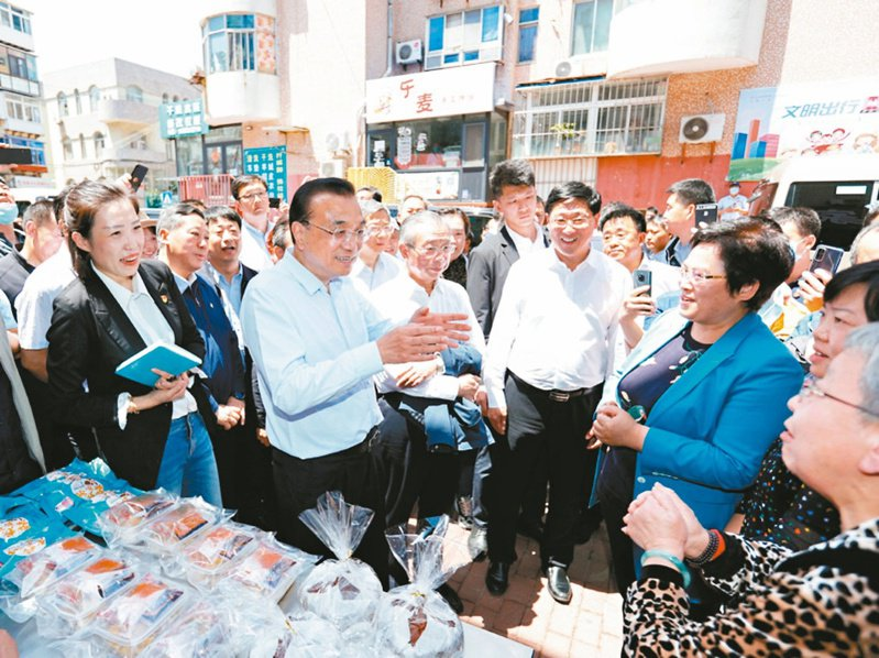 大陸國務院總理李克強到山東煙台視察小微企業,並大讚「地攤經濟」、「小店經濟」是就業崗位的重要來源,是中國大陸的生機。 取自中國政府網