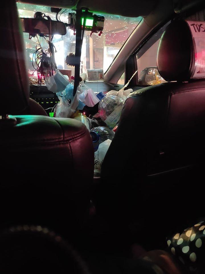 計程車的副駕駛座堆了滿滿的垃圾和瓶罐。圖擷自爆怨公社