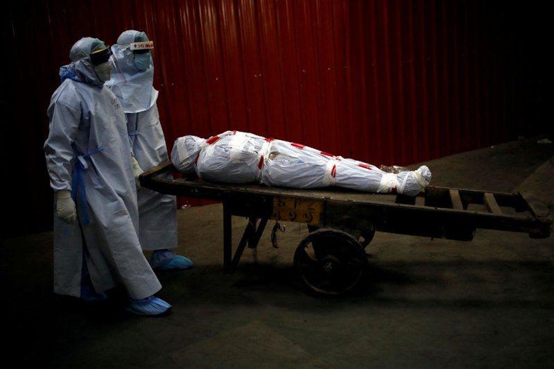 印度衛生部4日通報,過去24小時新增9304例新冠肺炎確診,創單日新高。圖為防疫人員將一名染疫病故者送往火化場。 路透社