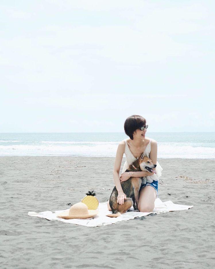 陳庭妮帶著愛犬、kate spade野餐系列鳳梨造型肩背包去海灘玩耍。圖/取自I...