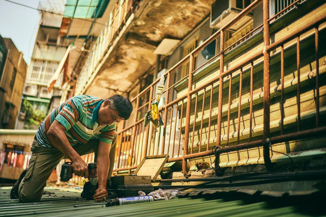 李銘順親自上陣在鐵皮屋頂修繕。圖/大慕影藝提供
