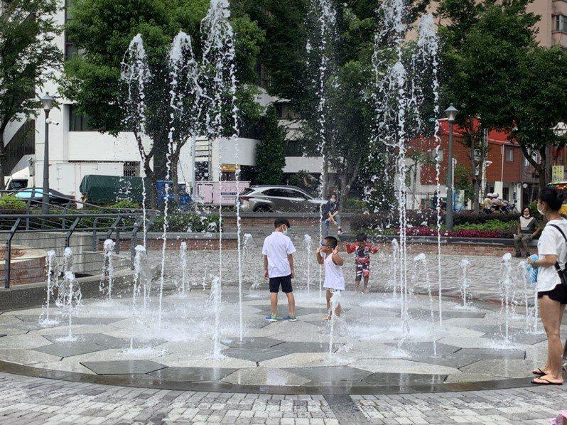 建成圓環噴泉每隔一小時會噴15分鐘,家長帶著孩子玩樂。記者趙宥寧/攝影