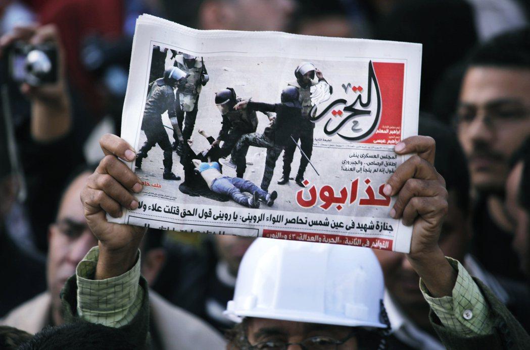 2011年12月,示威者高舉著,在頭版印有埃及軍警對女性示威者施暴的報紙。 圖/...