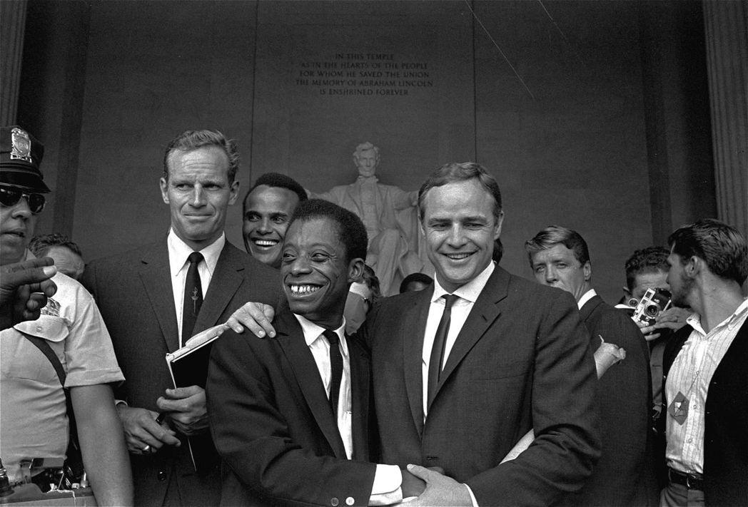 1963年的華盛頓遊行,與鮑德溫握手的人是影星馬龍白蘭度。 圖/美聯社