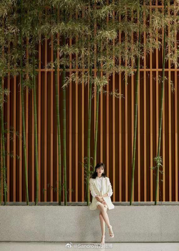 吳謹言身穿sandro米白色洋裝,選了一個拍照的好佈景。圖/取自微博