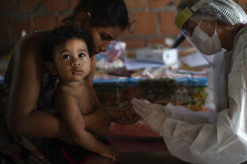 一名醫護人員為1歲幼兒進行新冠肺炎篩檢,快篩結果為陽性。 圖/美聯社