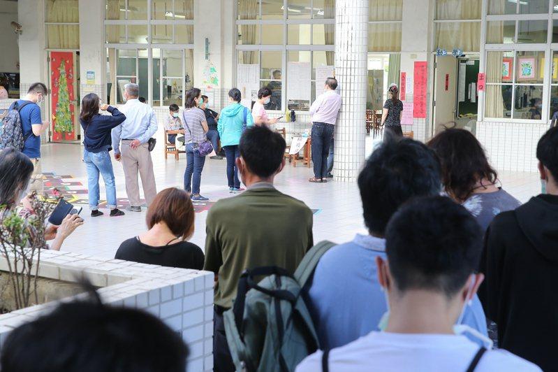高雄市長韓國瑜罷免案投票日,民眾遵守防疫規定戴口罩進行投票,一早大批民眾前來排隊投票。 圖/聯合報系記者季相儒攝影