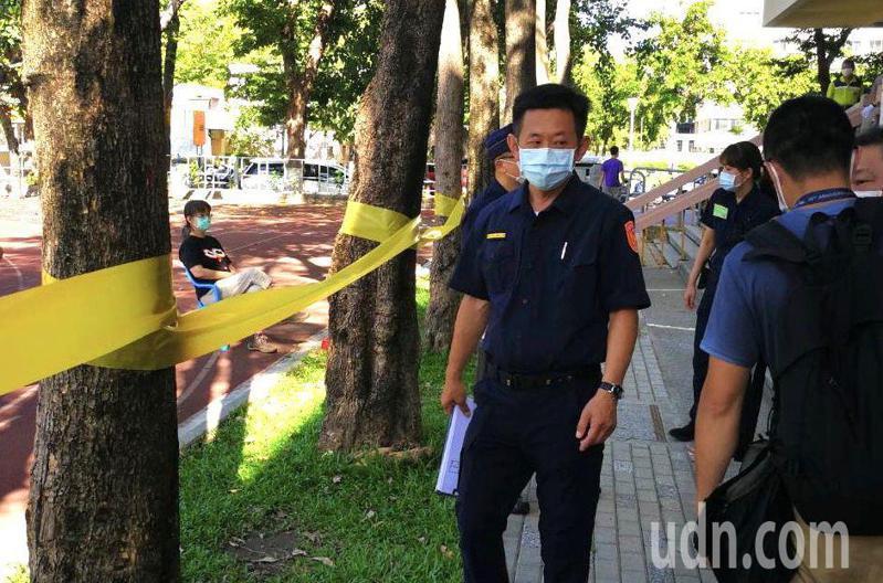 高雄市新興區信義國小1名女子(右)在投票所外,被檢舉「監看」投票,警方後來勸她退到30公尺外。記者林保光/翻攝