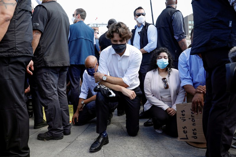 加拿大總理杜魯多5日出席國會山莊前的反種族主義活動,他帶著黑色口罩、右膝跪在地上以表支持。路透