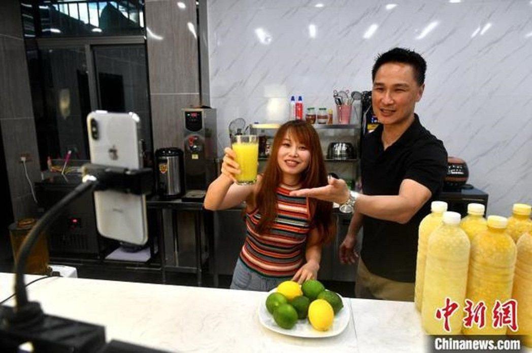 李正能(右一)正協助台青進行直播。圖/中新社