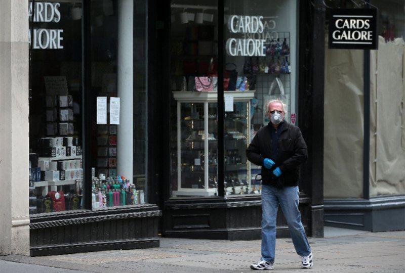 英國政府下調疫情警戒級別,考慮在7月初開放部分旅遊限制。圖為英國一名男子戴著口罩走過街頭。 法新社