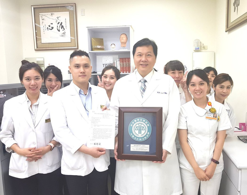 藝群醫學美容集團總裁王正坤醫師手拿102年首度獲得美容醫學品質認證獎牌與109年...