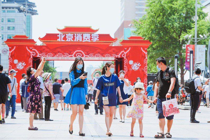 北京降低疫情防範級別,昨天在各區啟動消費季,圖為王府井大街上的遊客。 (中新社)