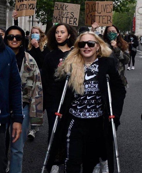 瑪丹娜拄著拐杖堅持出席倫敦示威遊行,力挺黑人平權,並且親切與抗議民眾合照。圖/摘
