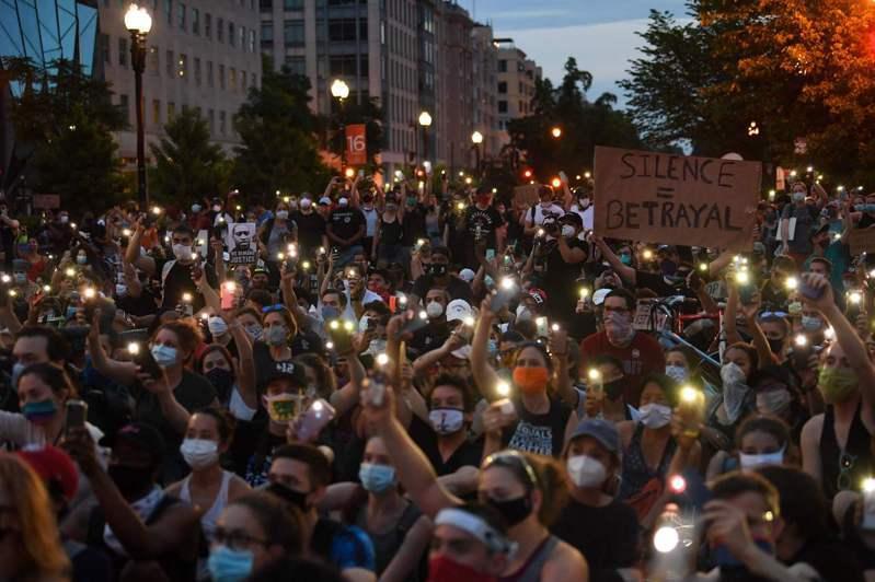 美國民眾3日在白宮前抗議非裔男子佛洛伊德遭白人警察壓頸致死案時,開啟手機手電筒哀悼。(法新社)