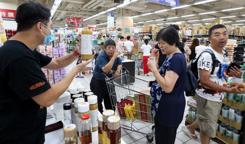 昨大解封日,賣場湧入大批購物人潮,民眾在賣場試喝蜂蜜商品。記者侯永全/攝影