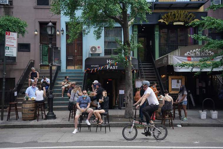曾是全球疫情震央的美國紐約將於八日解封,民眾七日坐在地獄廚房的餐廳外喝飲料。(法...