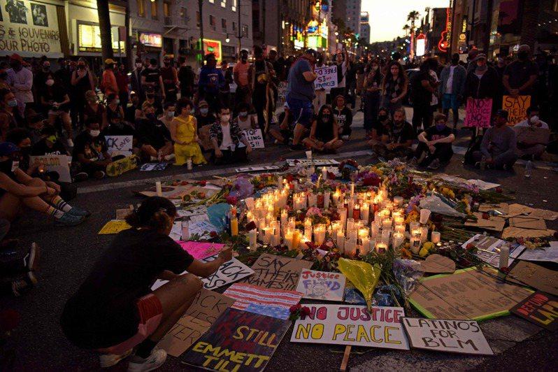 示威者7日在加州好萊塢街頭擺上鮮花與蠟燭,悼念遭警察壓頸致死的佛洛伊德和其他警察暴力受害者。(法新社)