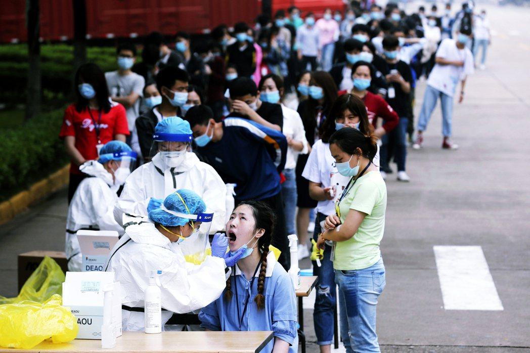 5月15日,武漢街頭上排隊檢疫的民眾。 圖/美聯社