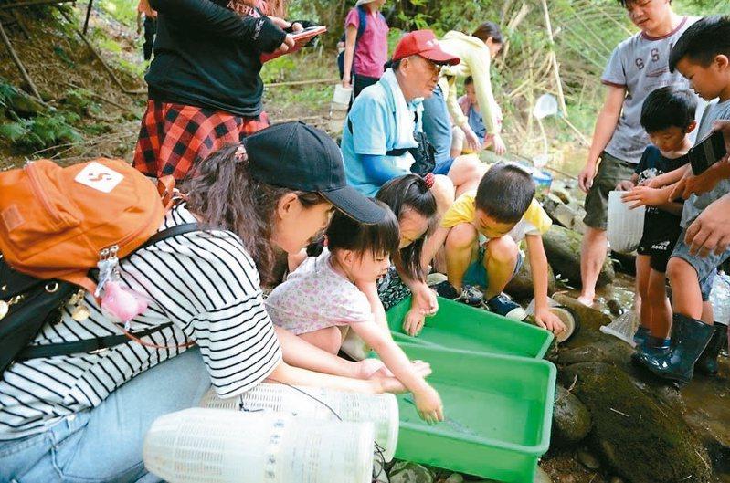 去年的「三代同遊國家公園」,親子觀看魚籠、蝦籠捕捉魚蝦的成果。圖/雪霸國家公園管理處提供