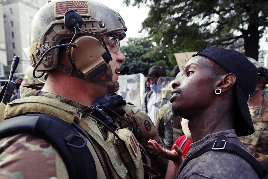 一名黑人示威者與國民兵,在白宮附近的街頭近距離對陣。 圖/美聯社