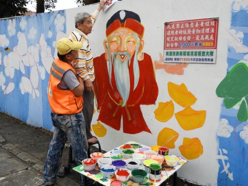 王菁華與志工團隊在內壢國小外牆畫上福德正神,希望改正亂丟垃圾的壞習慣。  圖/高...