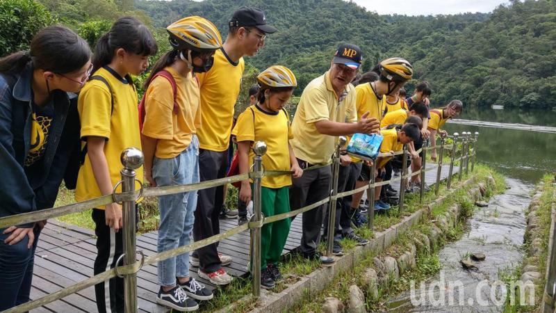 龍潭社區發展協會總幹事李志文向學生解說圓吻鯝魚的生態。記者戴永華/攝影