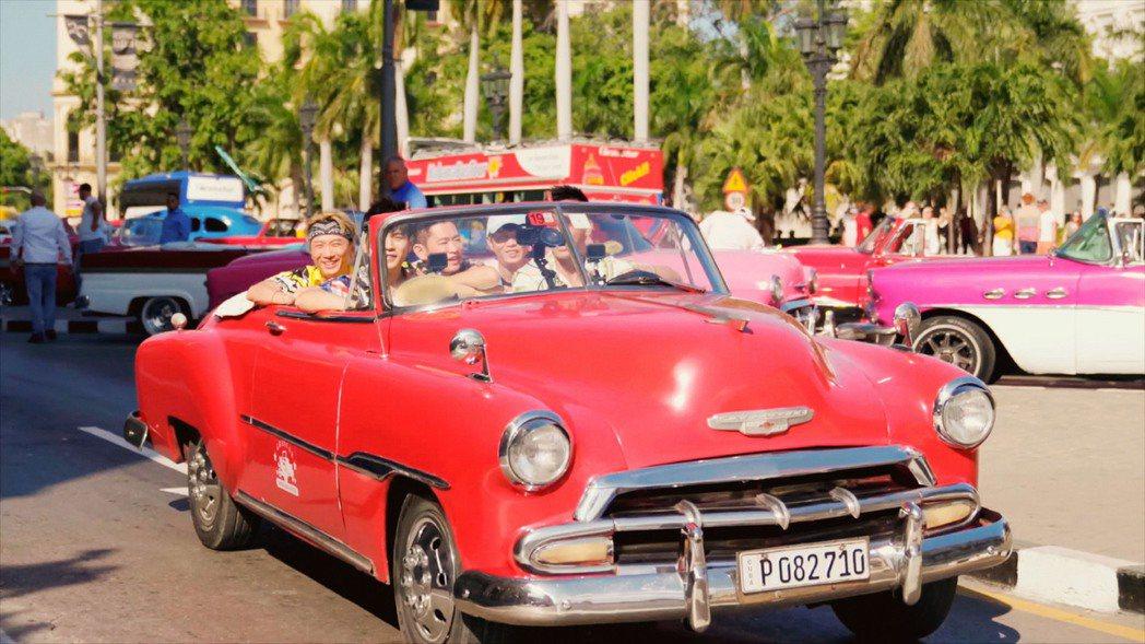 「周遊記」開紅色敞蓬復古跑車,造訪電影「玩命關頭8」開場拍攝地點。圖/Netfl