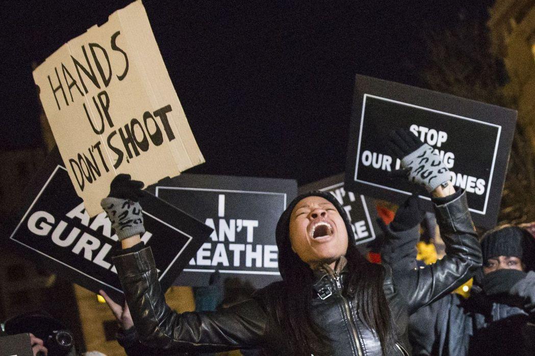 民眾高舉「Hands Up Don't Shoot」標語,攝於2014年12月。 圖/路透社
