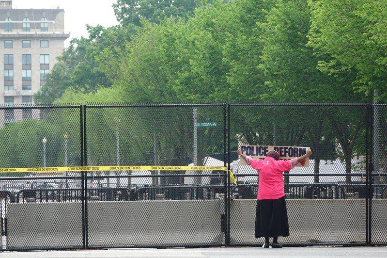 白宮周遭架起臨時圍欄隔絕示威活動,仍有民眾手舉標語抗議。華盛頓記者張文馨/攝影