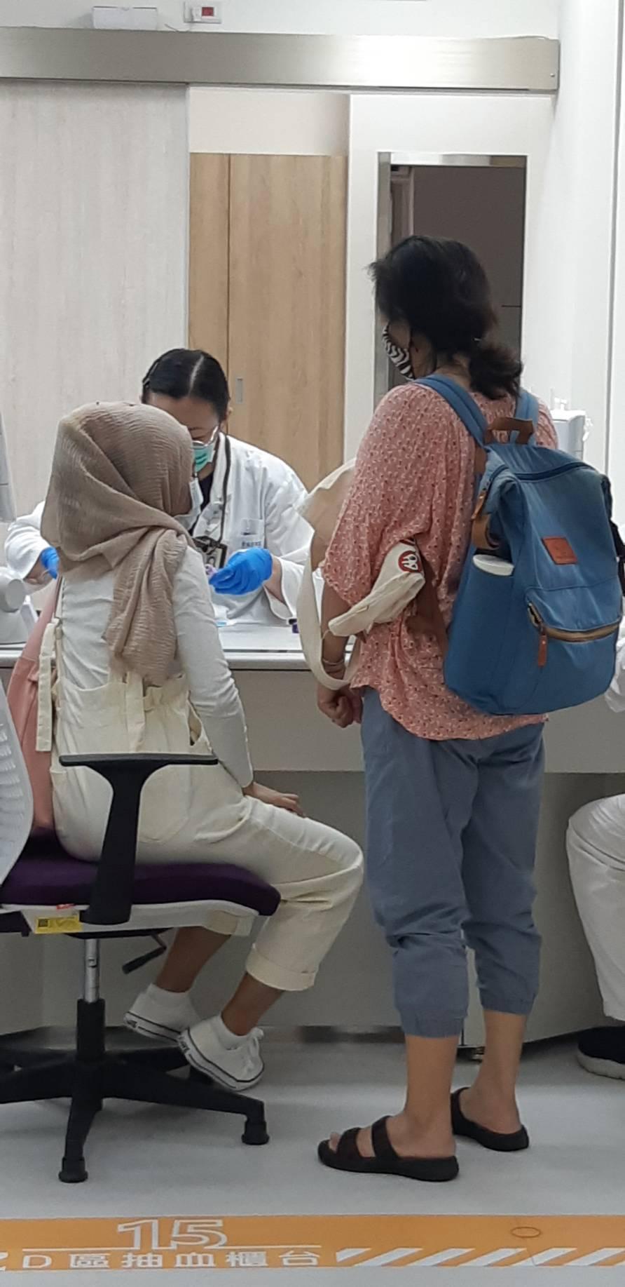 通譯莉莉(右)陪著莉娜(左)去抽血。記者邱宜君/攝影