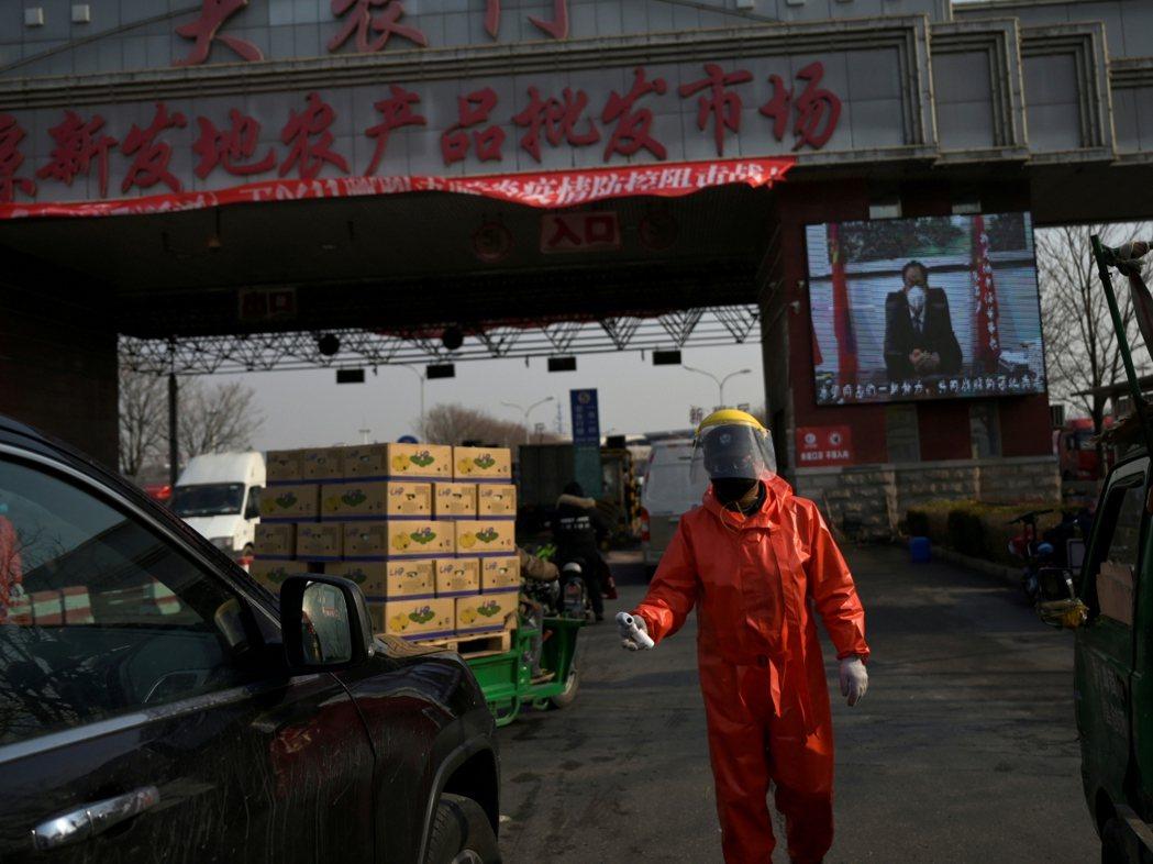 北京爆發疫情,當局派人在批發市場消毒。(路透社)