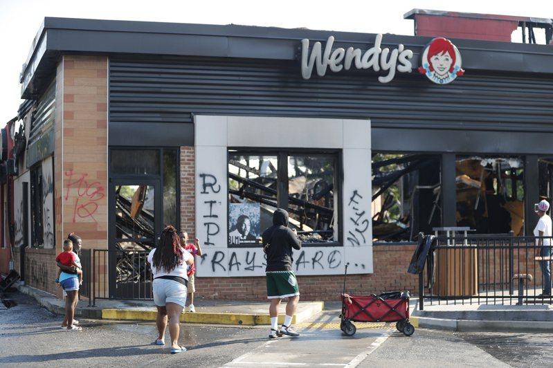 發生白人警察射殺非裔男子事件的亞特蘭大溫蒂速食店13日遭縱火燒毀,民眾14日在現場拍照。(歐新社)