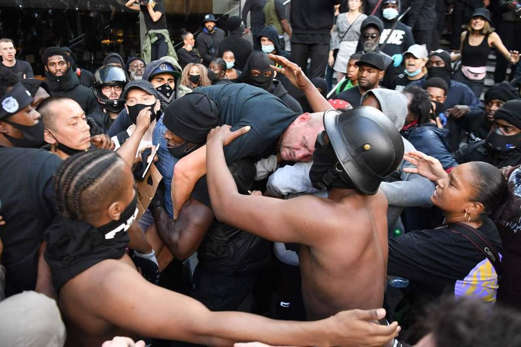一名極右派的白人男性,在樓梯間遭到其他示威者圍毆追打,此時在場的另一名黑人示威者...