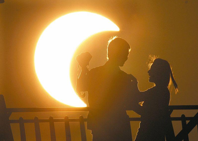 2012年5月的日環食景象,淡水漁人碼頭情人橋上一對情侶拿著相機記錄這難得一見的奇景。 圖/聯合報系資料照片
