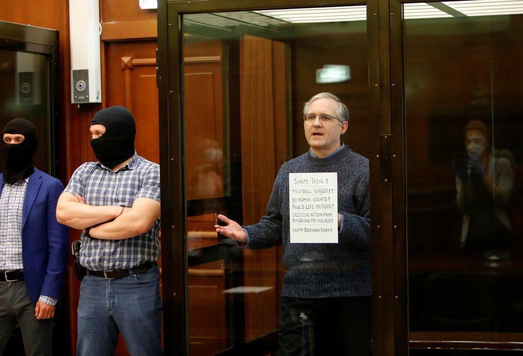 惠蘭15日站在莫斯科市法院被告籠裡,拿著「假審判」標語。(路透)