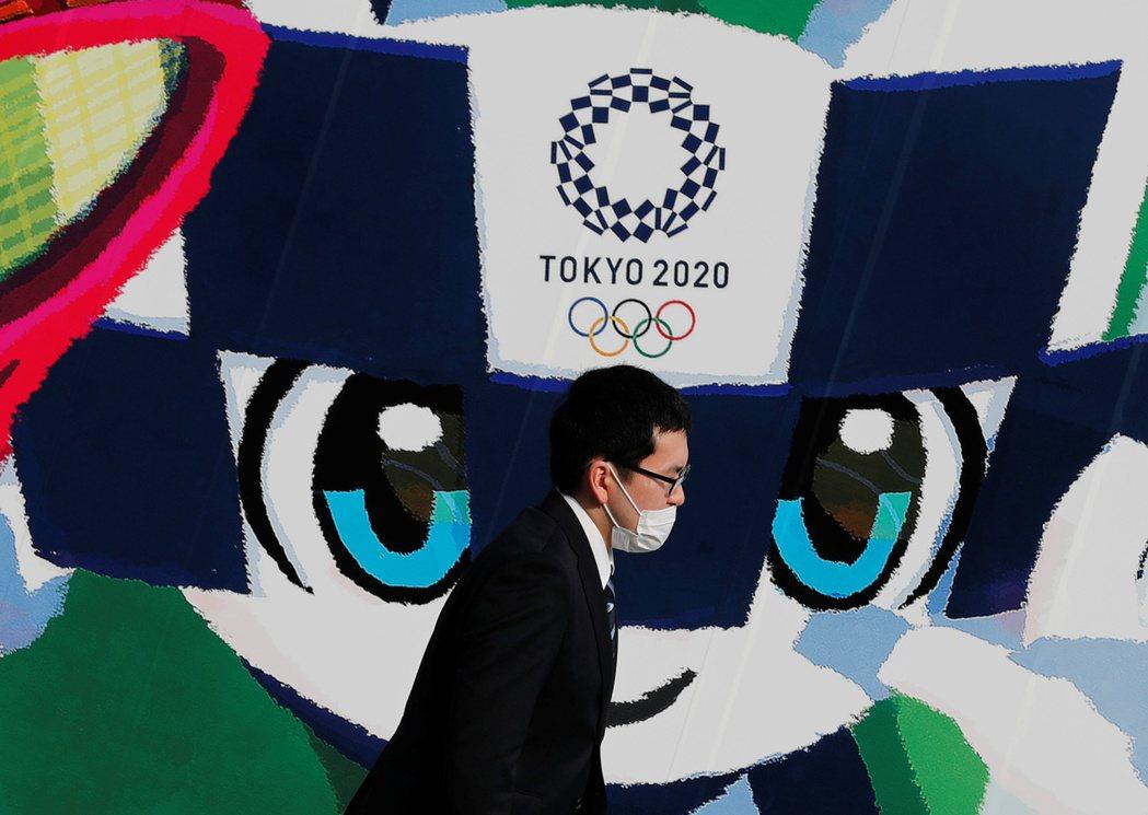 日本東京一名戴口罩的男子經過東京奧運大型海報。(路透)