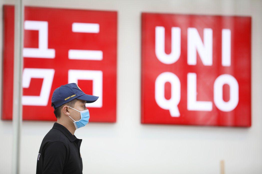 Uniqlo在越南河內第一家門市3月6日開幕,一名保全戴口罩站在外面。(歐新社)
