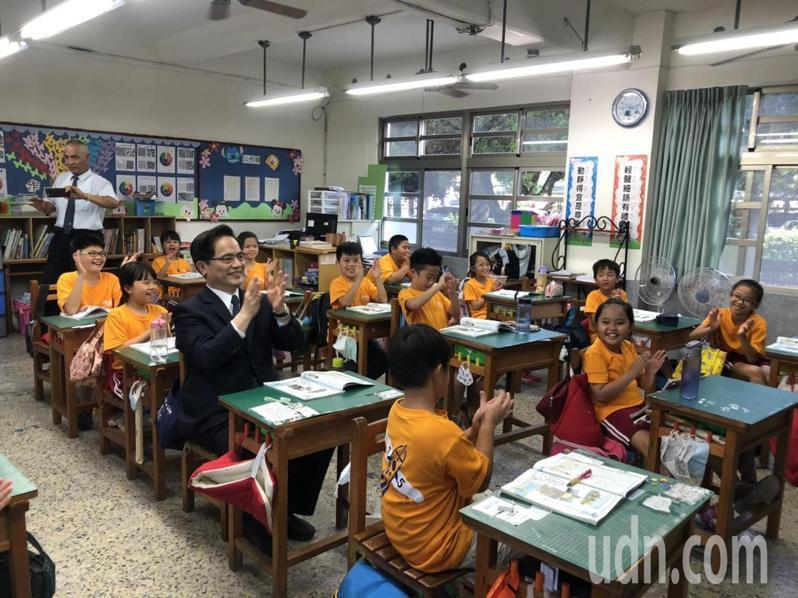 林欣榮回到母校台南將軍漚汪國小, 坐在座位上重溫昔日上課點滴。圖/學校提供