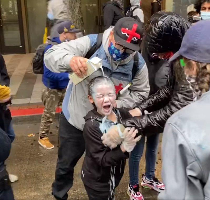 美國一名7歲男童和家人參加遊行時遭到警方噴胡椒噴霧,路人見狀趕緊用水和牛奶清洗。 圖/翻攝自Evan Hreha臉書