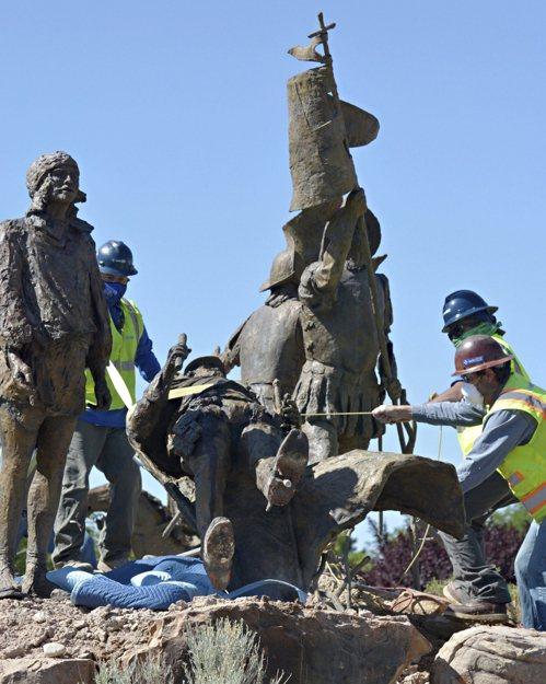 反警察暴力團體在新墨西哥州首府阿布奎基市15日以鎖鍊纏身,試圖推倒一座殖民時期 西班牙征服者的雕像,但遭到當地民兵以武力守護雕像。 美聯社