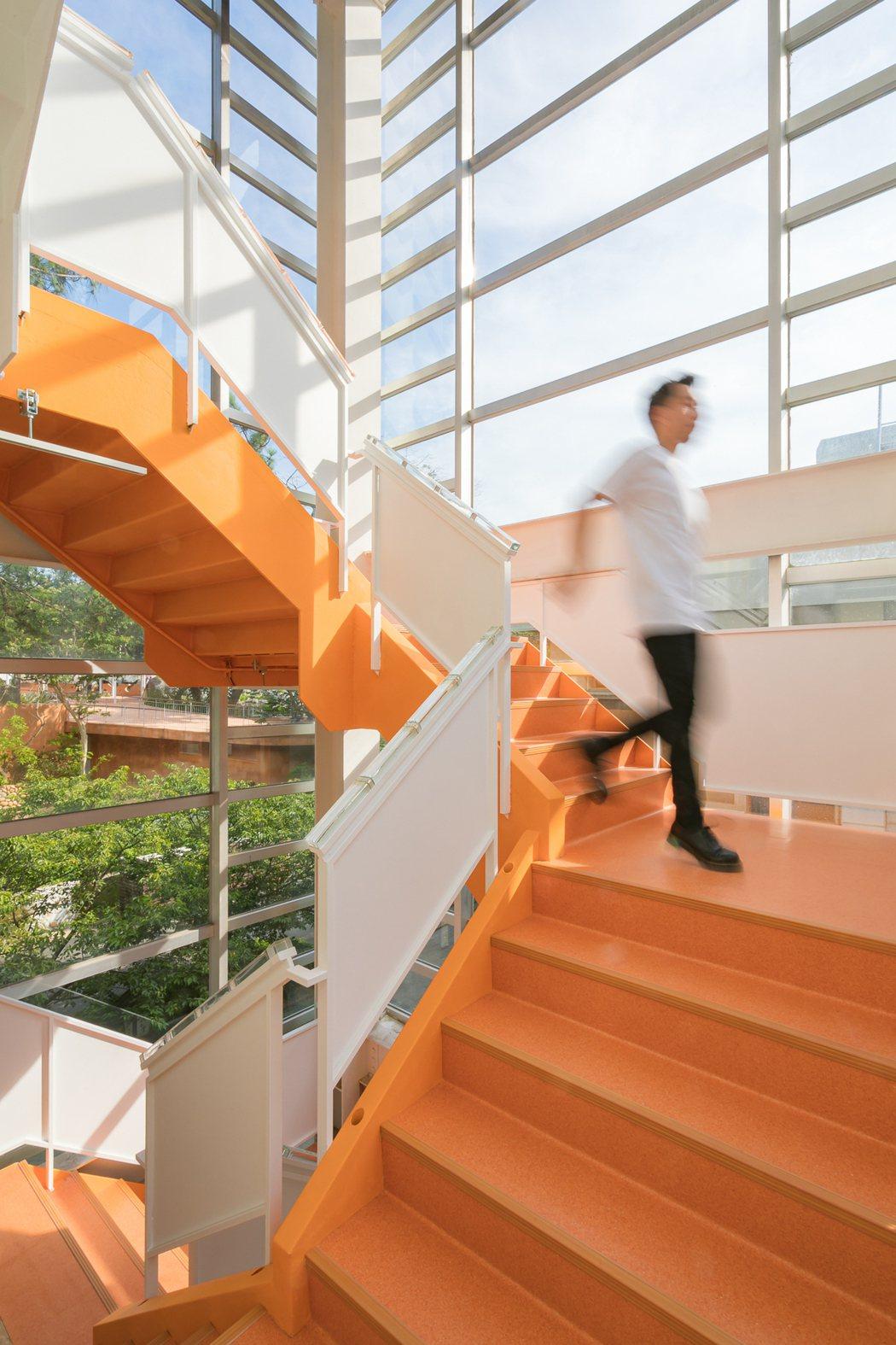 連結三樓到一樓的橘色迴轉樓梯正像是從窯爐舀出、高溫流動的玻璃膏,從高處往下流散,...
