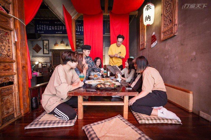 中國風格木造坐舖中店主正熱情解說料理菜單,適合親友相約聚餐。(飲酒過量,有害健康)