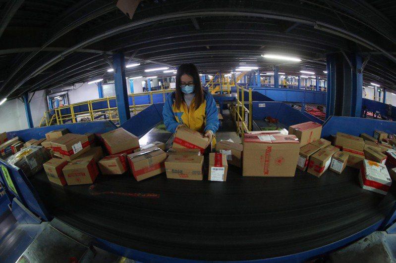 6月18日凌晨,在電商線上直播帶貨的同時,眾多物流工人連夜在蘇寧易購北京物流基地對網上下單的商品進行分揀、裝車。(中新社)