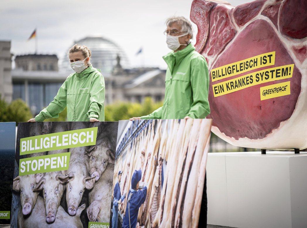 圖為在柏林的聯邦總理府前,環保示威者舉牌指控:過度便宜的肉品,導致了德國肉廠病態...