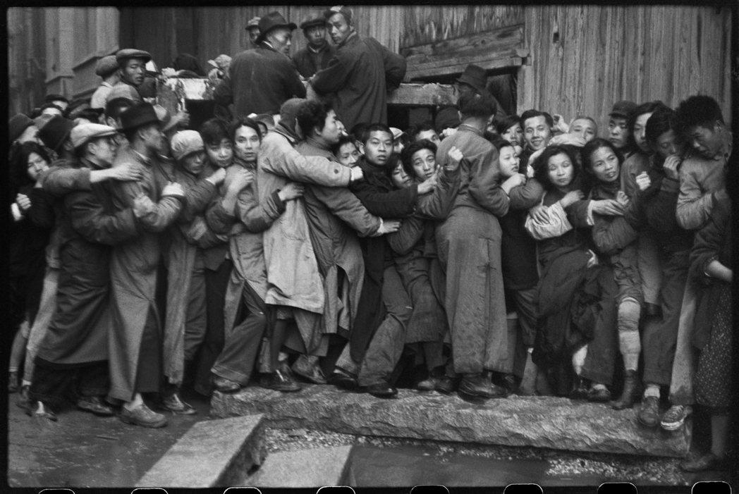 布列松拍下了一張民眾前胸貼後背,擠在銀行前要換購黃金的寫實照片,成為當時世界認識...
