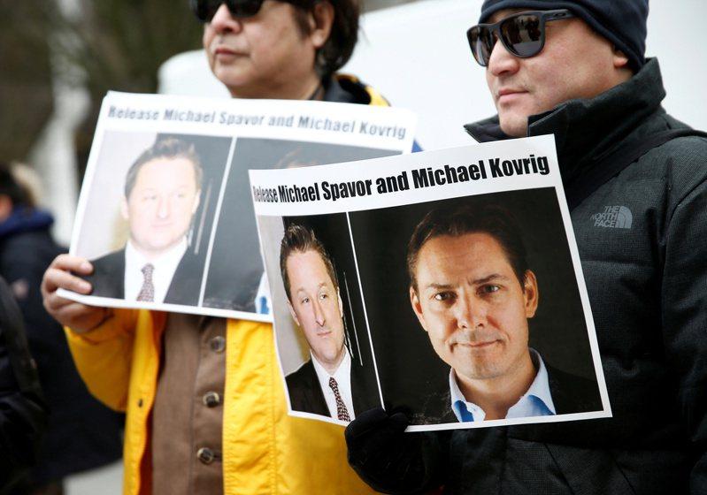 圖為2019年3月6日,在孟晚舟引渡聽證會場外,有民眾手持康明凱(右)及斯帕弗相片,呼籲北京當局釋放兩人。(路透)