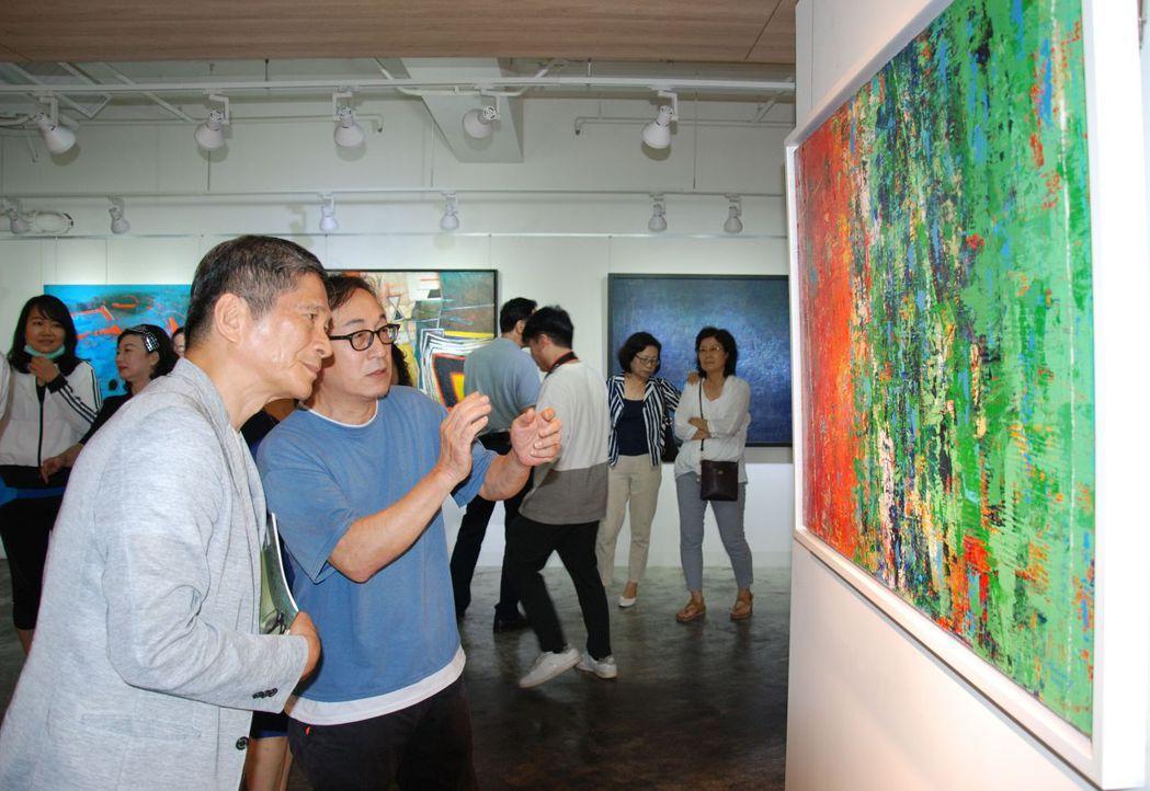 文化部長李永得(左)專注聆聽藝術家介紹作品。 楊鎮州/攝影