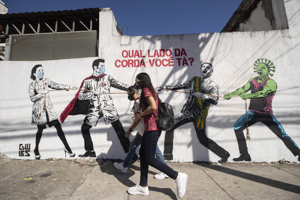 兩名戴口罩民眾十九日行經聖保羅市區一處描繪醫護奮戰病毒的壁畫。(美聯社)